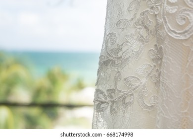 a48c20d42ba A beautiful wedding dress hangs in front of a window illuminated by warm  light with a