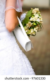 Beautiful wedding dress on a bride with veil, white handbag and beautiful bouquet in hands.