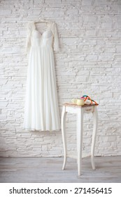 Beautiful wedding dress on hanger, in natural light from window on background white brick wall