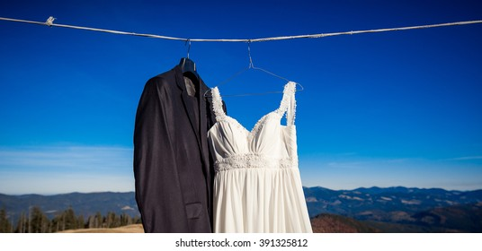 Beautiful wedding dress and suit hanging on hanger. Amazing mountain landscape background