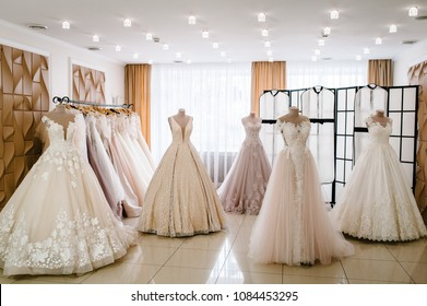 Beautiful wedding dresses, bridal dress hanging on hangers and mannequins in studio, shop. Fashion look. Interior of bridal salon. Wedding show room trendy, modern.