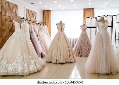 Beautiful wedding dresses, bridal dress hanging on hangers and mannequin in studio. Fashion look. Interior of bridal salon.