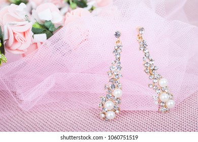 Beautiful wedding earrings on a pink background