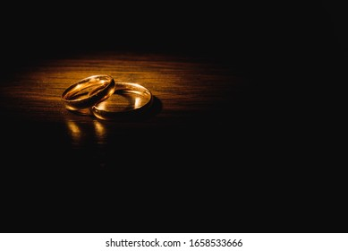 Beautiful wedding gold rings on dark background