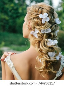 beautiful wedding hairstyle on light hair. Greek braid of curls with a decoration in the hair. evening hairstyle with braided