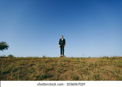 Beautiful wedding photosession. Handsome bridegroom in a black suit and white shirt with a bouquet of the bride stands on a stone on walk around the big green field against blue sky background.