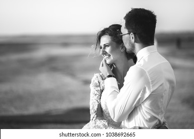 Beautiful wedding photosession. Handsome unshaved groom in white shirt kisses his young cute smiling bride in lace pattern dress with exquisite hairstyle on walk along the coastline. Black and white