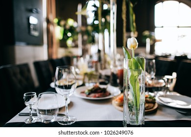 Beautiful wedding restaurant table decoration with fresh flowers and  Tulip in the water