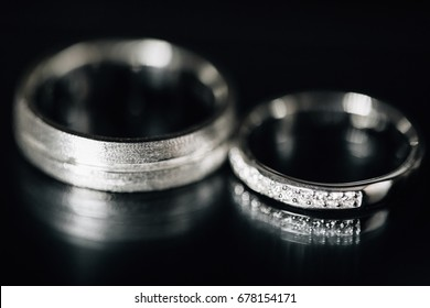 beautiful Wedding rings reflected on a black glossy background. Gorgeous jewelry