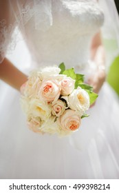 Beautiful wedding rose bouquet close-up in the bride's hands.
