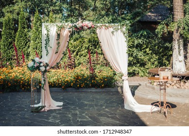 A beautiful wedding is set up. Square wedding ceremony. The rectangular arch is decorated with flowers, greenery. Nice, trendy floral decor. Part of the festive decor, floral arrangement.