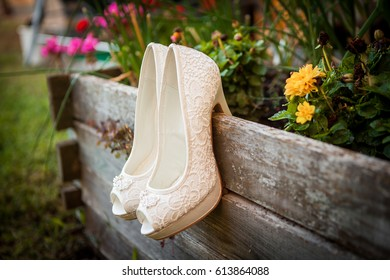 Beautiful wedding shoes hang on a wooden pot. The shoes hang on the tree. Attribute of the bride. Lacy white shoes. An open toe.