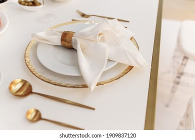 beautiful wedding tableware lies on a white table. gold spoons and forks. wedding decorations. banquet table. empty plate