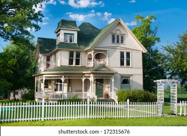 A beautiful and well maintained two story country home with white picket fence stands on the edge of a small rural town in Wisconsin.
