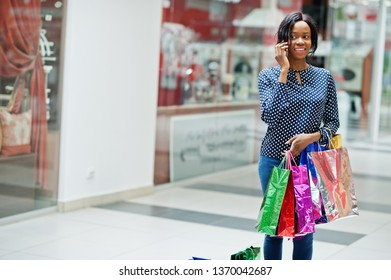 Beautiful well-dressed afro american woman customer with colored shopping bags, speaking on phone at mall.