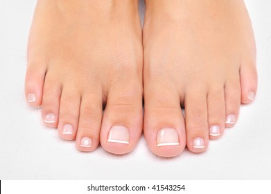 Beautiful well-groomed female feet with the French pedicure