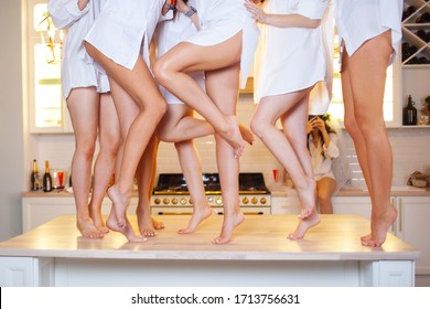 Beautiful and well-groomed female legs. Group of girlfriends with beautiful bare feet dancing on the table, women's party