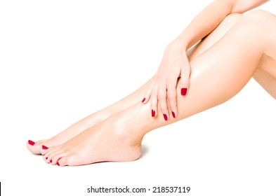 Beautiful well-groomed female legs with red pedicure isolated on white background