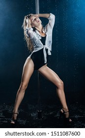 Beautiful wet athletic busty elegant blonde girl performs artistic elements of an exotic dance on the rain in a theatrical smoke. Health, lifestyle, sports design. Copy space
