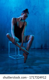 Beautiful wet ballerina in black underwear and pointes sitting on white cube, loft interior. Young artist posing in studio, isolated on blue background. Concept of beauty and ballet art.