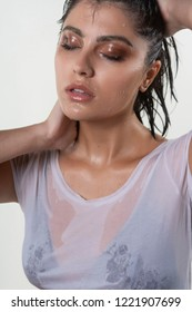 Beautiful wet brunette girl with water drops running down her face, wearing a white translucent T-shirt, through which a black bra shines through. Isolated on white background. Natural makeup.
