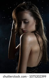 Beautiful wet slim girl wearing a black translucent lingerie posing in rain water drops in a studio on black background in a theatrical smoke. Smooth healthy wet skin. Copy space.