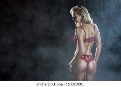Beautiful wet sporty big tits tanned blonde girl wearing red underwear posing from the back in scenic smoke and fog under falling water drops of rain on black. Healthy smooth skin. Copy space.