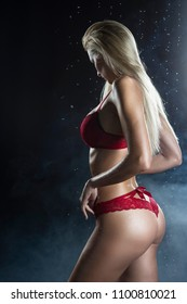 Beautiful wet sporty big tits tanned blonde girl wearing red underwear posing sideways in scenic smoke and fog under falling water drops of rain on black. Healthy smooth skin. Copy space.