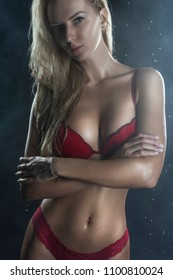 Beautiful wet sporty big tits tanned blonde girl wearing red underwear posing in scenic smoke and fog under falling water drops of rain on black. Healthy smooth skin. Copy space.Advertising design.