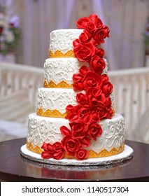 Beautiful white 4 layers wedding cake decorated with red fondant roses