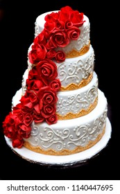 Beautiful white 4 tier wedding cake decorated with red fondant roses