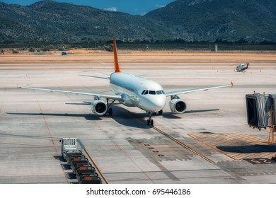 Beautiful white airplane on the runway in Dalaman airport. Landscape with big passenger airplane is taking off and mountains at bright sunny day in summer. Business trip. Commercial aircraft. Travel