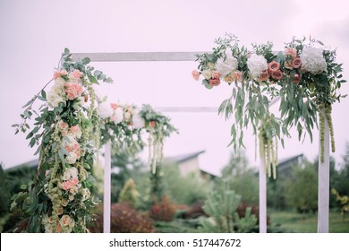 beautiful white arch with flowers standing outdoors for wedding ceremony