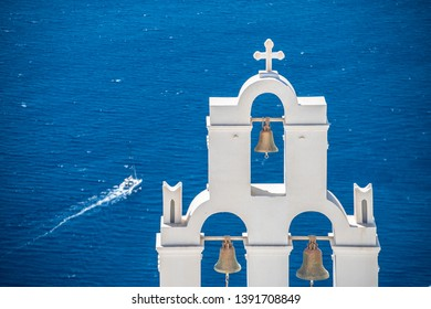 Beautiful white bell tower with 3 bells with blue Mediterranean sea and yacht in the background.