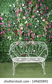 Beautiful white bench stands near to green hedge with small flowers.