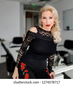 A beautiful white blonde woman with light green eyes red lipstick in a black slim top with  lace sleeves and decolletage, leggings with rose embroidery, sitting at the edge of a desk in the office