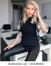 A beautiful white blonde woman with light green eyes and rose-gold lipstick in an animal print sleeved blouse and a black leather slim leggings sitting on the desk in the ofice, touhing her hair