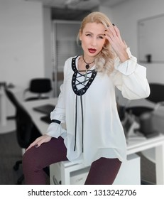 A beautiful white blonde woman with light green eyes and dark red lipstick in a  white silk blouse with black leather  ornaments and slim leggings sitting on the desk in the ofice, touhing her hair