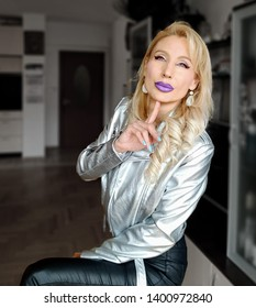 A beautiful white blonde woman with light green eyes and wavy blonde hair with light green eyes and lilac lips in black leather trousers and silver jacket