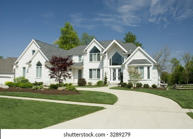 Beautiful white brick home featuring a very modern architectural design with large windows and beautiful  landscaping.