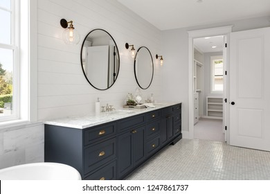 Beautiful White and Bright Bathroom in New Luxury Home with Large Vanity and Dark Blue Cabinets.Features Bathtub and Two Sinks, and Circular Mirrors. Shows Walk-In Closet