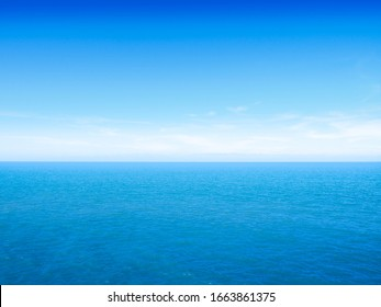 Beautiful white clouds on blue sky over calm sea with sunlight reflection, Bali Indonesia. Tranquil sea harmony of calm water surface. Sunny sky and calm blue ocean. Vibrant sea with clouds on horizon