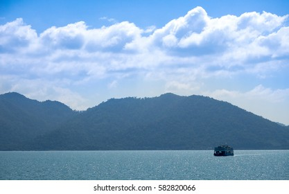 Beautiful white clouds on blue sky over calm sea with boat and sunlight reflection, PP Island thailand.