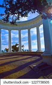 Beautiful white colonnade on Tsar's Path or Sunny path or the Solnechnaya tropa, trees, blue sky with clouds , Crimea