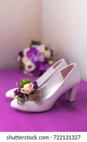 4080ebb8fe3 Beautiful white female wedding shoes with a heel standing on a purple table  with a flower