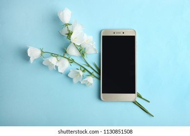 Beautiful white flowers bells and a modern smartphone on a blue background. Top view.