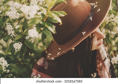 beautiful white flowers on hat of hipster girl in green leaves with bloom in evening sunshine. stylish woman traveler calm relax in spring garden. space for text. atmospheric moment