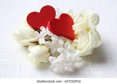 Beautiful white flowers and red hearts on white background.