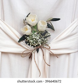 Beautiful white flowers. Tulips and gypsophila. Arrangement in draped fabric.