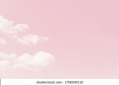 Beautiful white fluffy clouds on a pale pink sky background